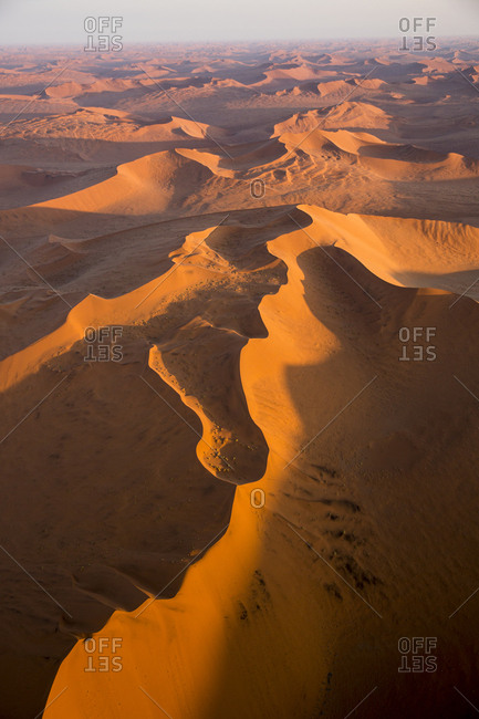 Africa, Namibia, Namib Naukluft National Park, Aerial view of morning sun lighting windblown red sand dunes in Namib Desert near Sossusvlei