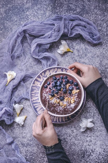 Woman eating blueberry smoothie bowl topped with blueberries, walnuts, cacao nibs and coconut