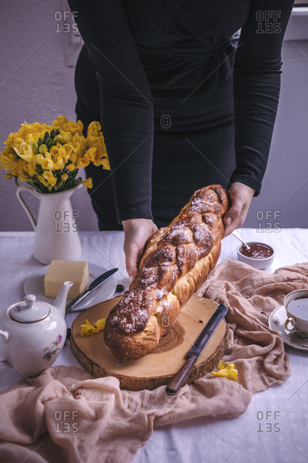 Woman holding a braided sweet Easter bread served for breakfast with butter and jam