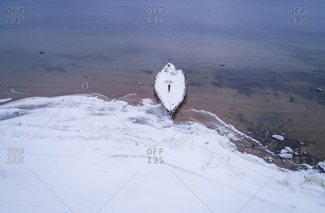 Aerial view of a man on a wooden shipwreck on the beach of Kasispea, Estonia