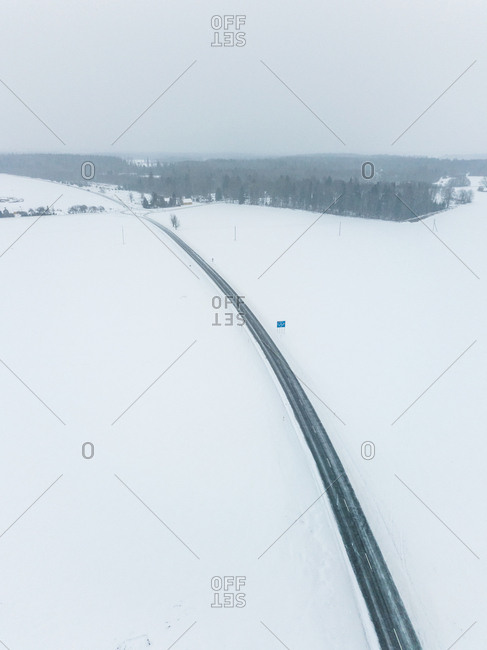 Aerial view of an empty road in the middle of the nordic landscape in winter, Estonia
