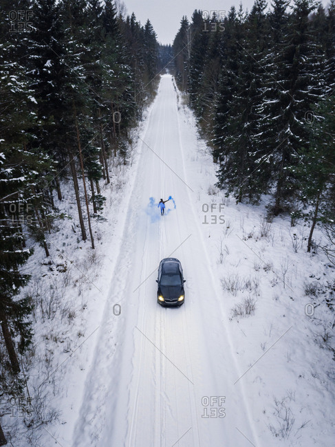 Aerial view of a man lighting a blue smoke grenade on a snowy road in the forest, Estonia
