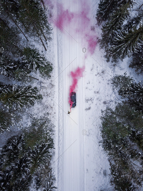 Aerial view of a man lighting a pink smoke grenade on a snowy road in the forest, Estonia