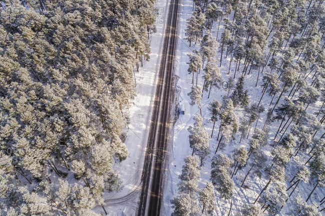 Aerial view of an empty straight road in the forest of Naage, Estonia