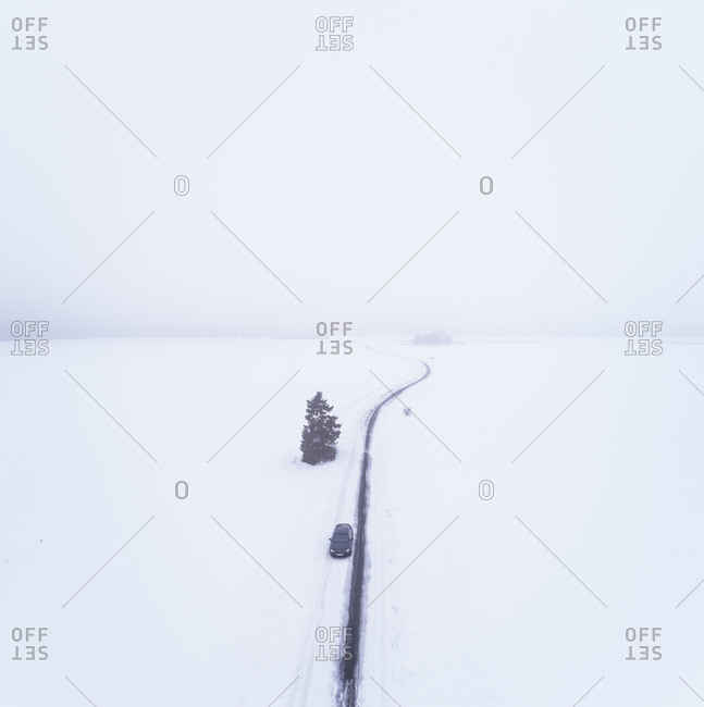 Aerial view of a car driving on a snowy road in the blizzard on Vormsi island, Estonia