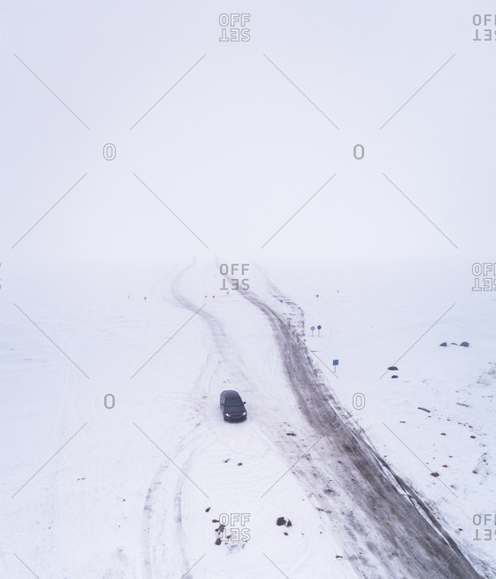 Aerial view of a car driving on a frozen road in the Blizzard in Rohukula, Estonia