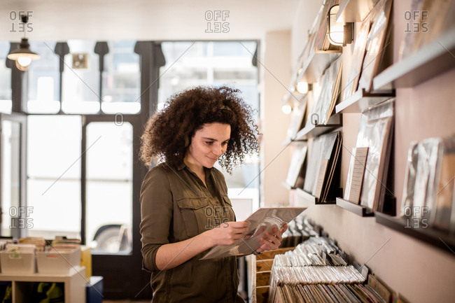 Young adult female holding record in a store