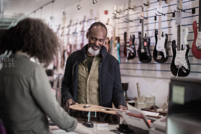 Senior male buying an acoustic guitar