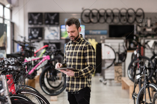 Small business owner using digital tablet in a cycle store