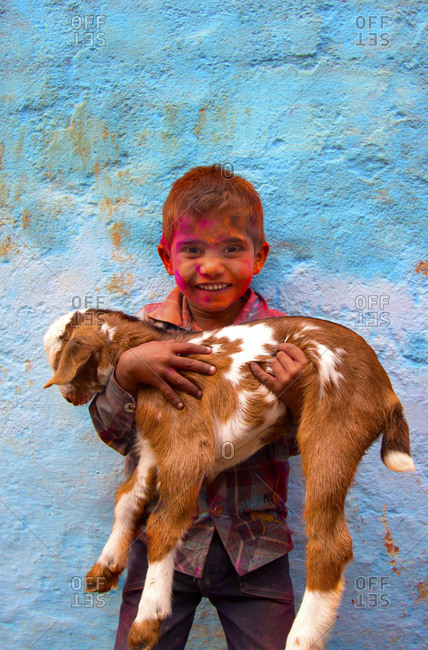 Mathura, India - March 5, 2015: Young boy holding a small goat during Holi celebrations