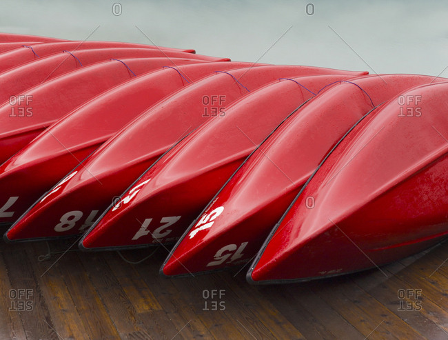 Red rental canoes stacked along wooden dock