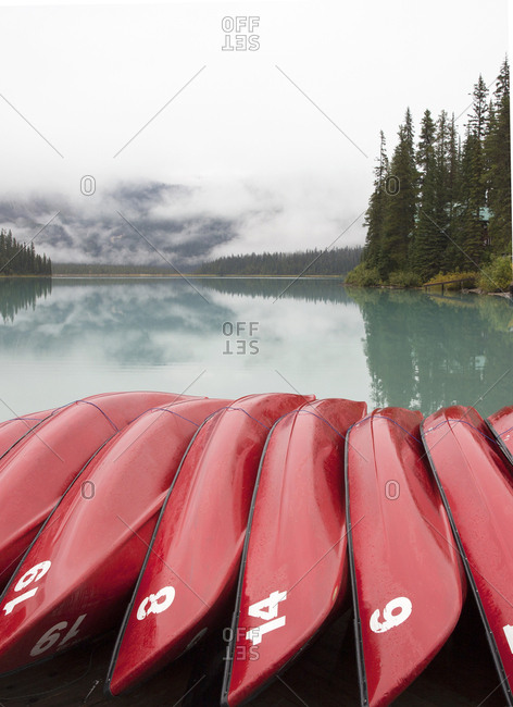 Red rental canoes stacked on lakeshore dock