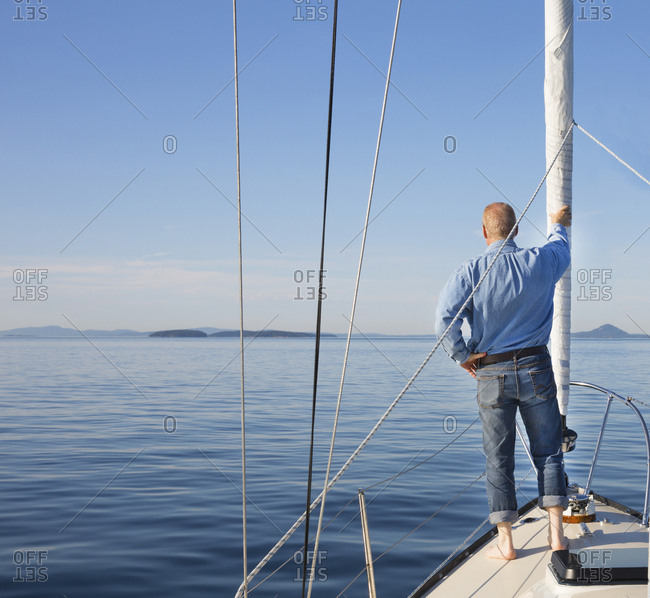 Man standing on the edge of a sailboat sailing toward the San Juan Islands