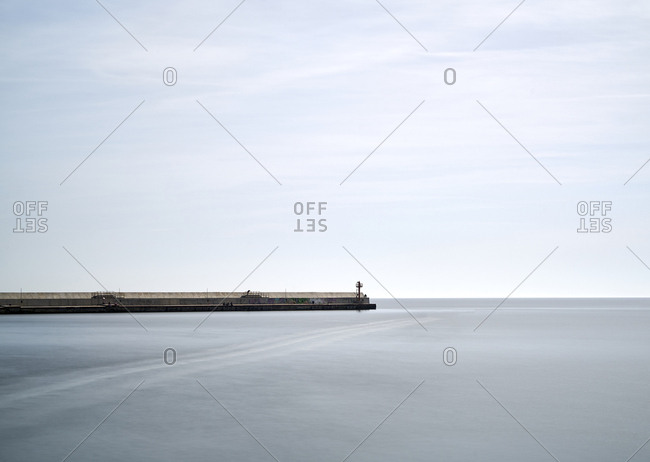 Balchik, Bulgaria; April 05 2018; A pier and a small lighthouse at a small local harbor on calm sea. Balchik is a Black Sea coastal town and seaside resort in the Southern Dobruja area of northeastern Bulgaria.