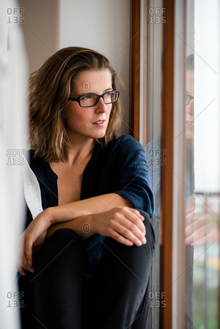 Young woman sitting near window and looking out