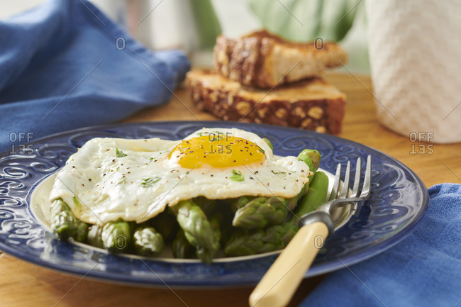 Healthy breakfast of fried egg and asparagus with whole grain toast