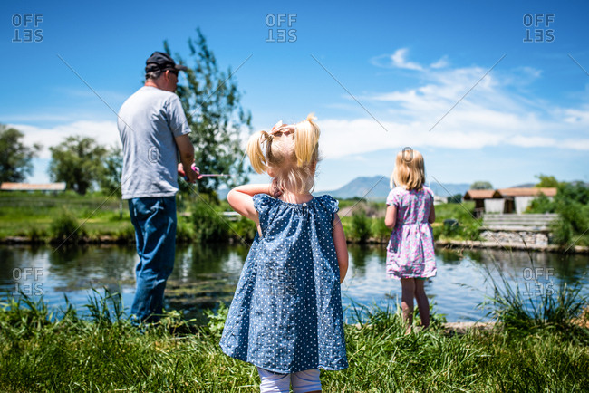 Grandfather showing granddaughters how to fish