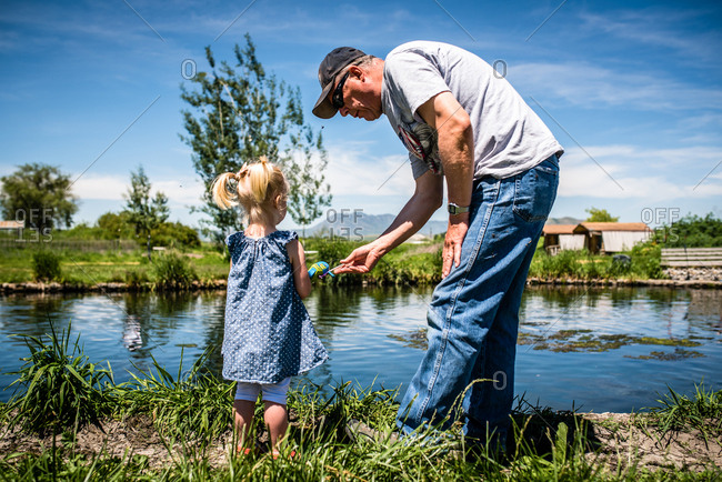 Grandpa and grandchild fishing in a pond