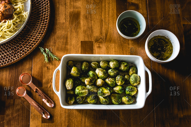 Top view of cooked Brussels sprouts and side items on wood table