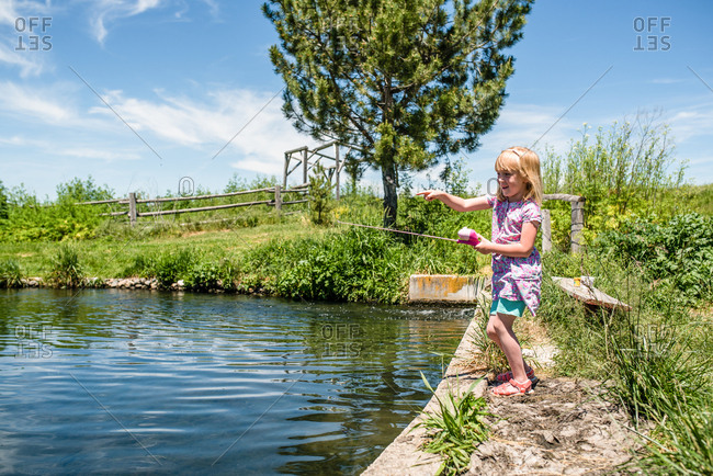 Young girl with fishing pole pointing at pond