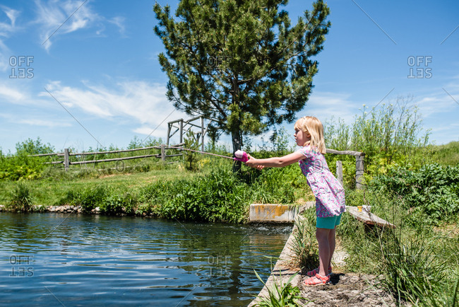 Blonde girl casting fishing pole on sunny day