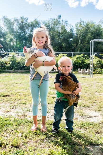 Siblings hugging chickens in the backyard