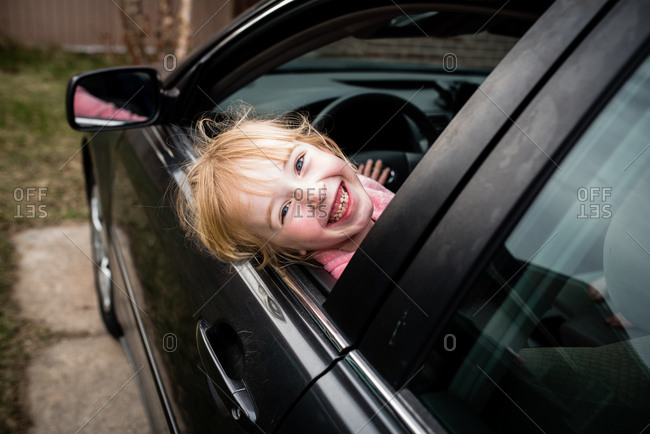 Silly girl hanging out of parked car window