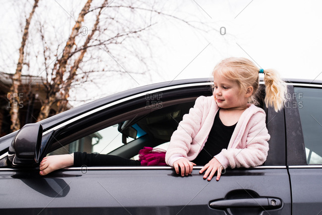 Blonde toddler playing in parked car in driveway