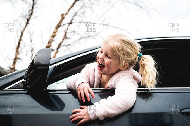 Playful toddler having fun pretending to drive