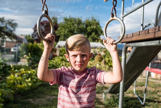 Serious boy holding metal rings on swing set