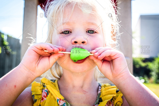 Little girl eating neon popsicle on summer day