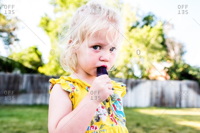 Shy girl eating grape popsicle in backyard