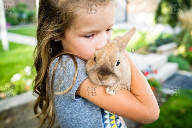 Girl kissing side of bunny rabbit's head stock photo - OFFSET