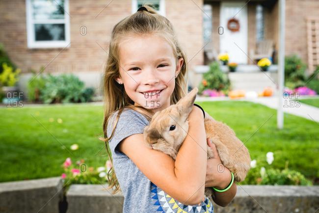 Smiling girl hugging pet bunny