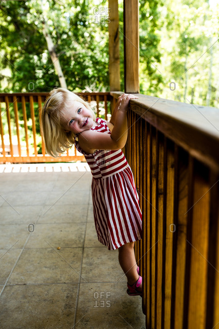 Playful girl hanging from wooden railings on back deck
