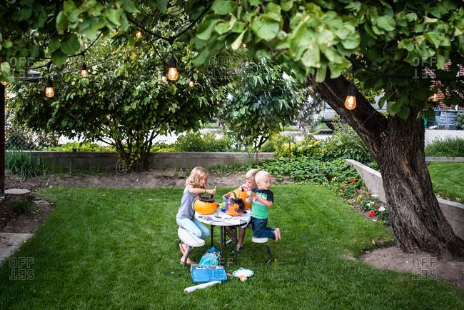 Kids painting pumpkins at picnic table outside