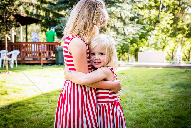 Blonde sisters hugging on Independence Day