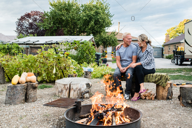 Married couple sitting by fire pit in backyard