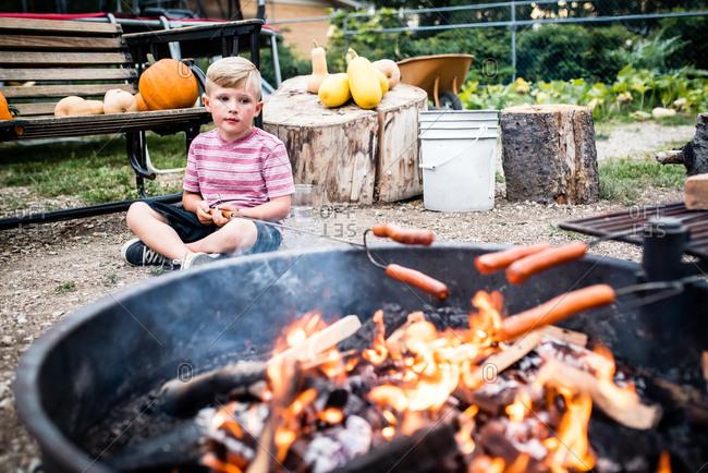 Boy roasting hot dogs in backyard