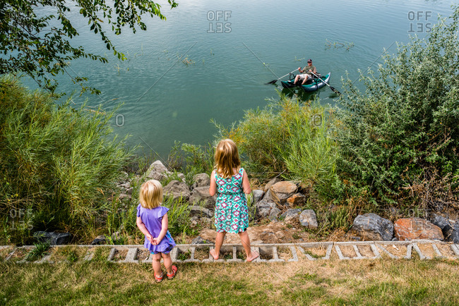 Little girls looking out at grandfather in a boat on a lake