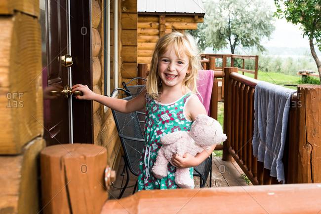 Happy little girl opening door to cabin