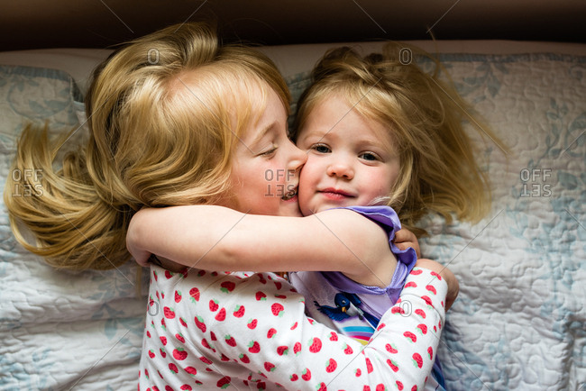 Girl kissing her little sister