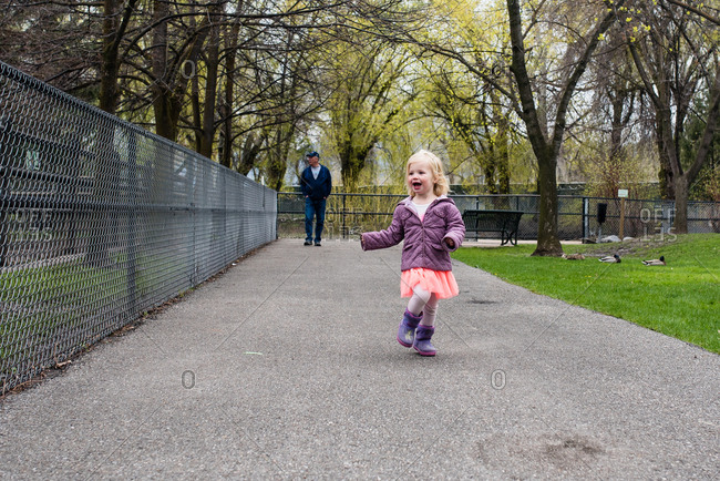 Girl walking on path at the zoo with grandfather trailing behind