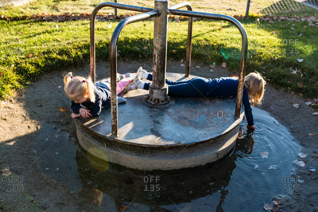 Girls playing on a merry-go-round at a park surrounded by a puddle