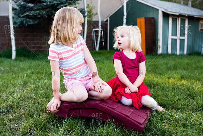 Two little girls looking at one another with a surprised look