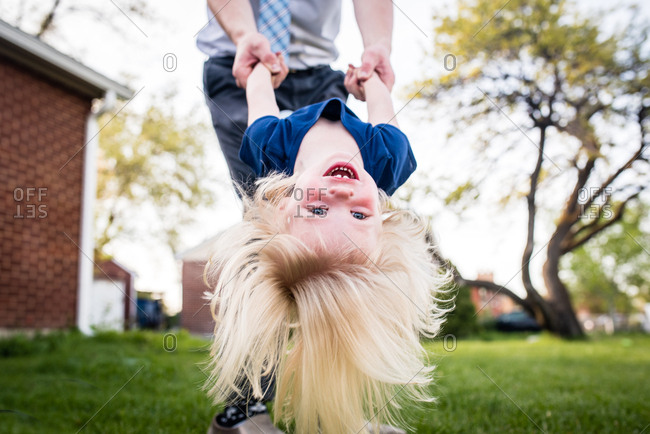 Man tipping little girl upside down