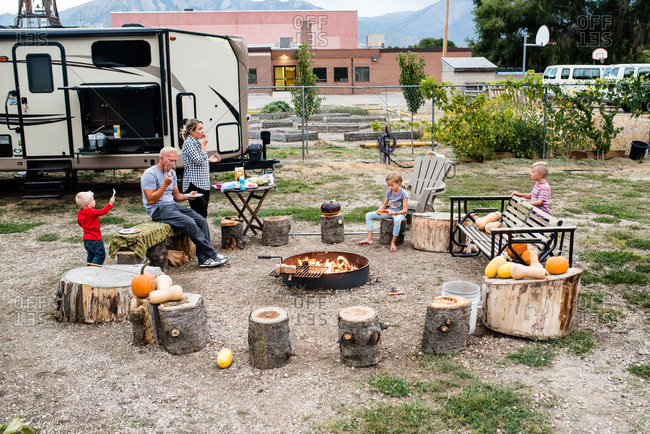 Family eating dinner outdoors by camp fire