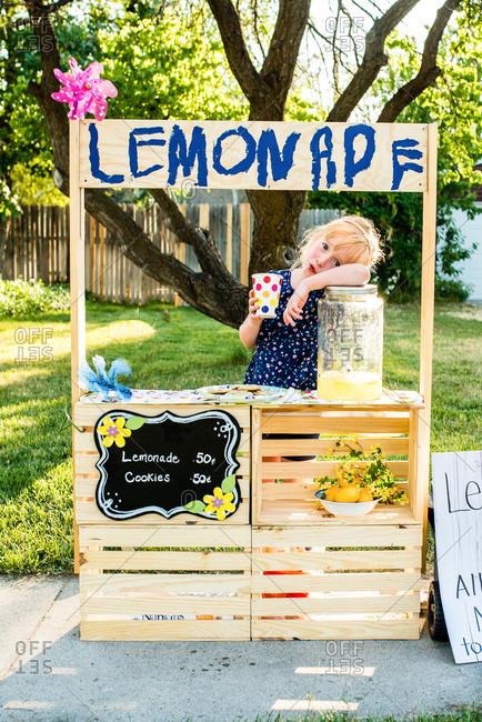 Little girl manning her lemonade stall on sidewalk outside house