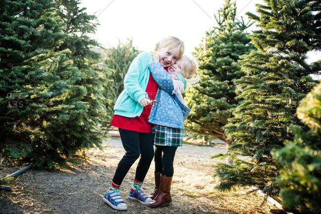 Little girl giving older sister big hug while looking for Christmas tree