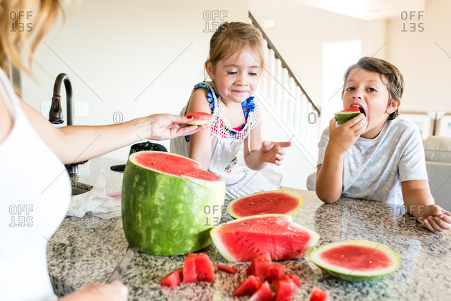 Brother takes big bite of watermelon as sister looks on skeptically
